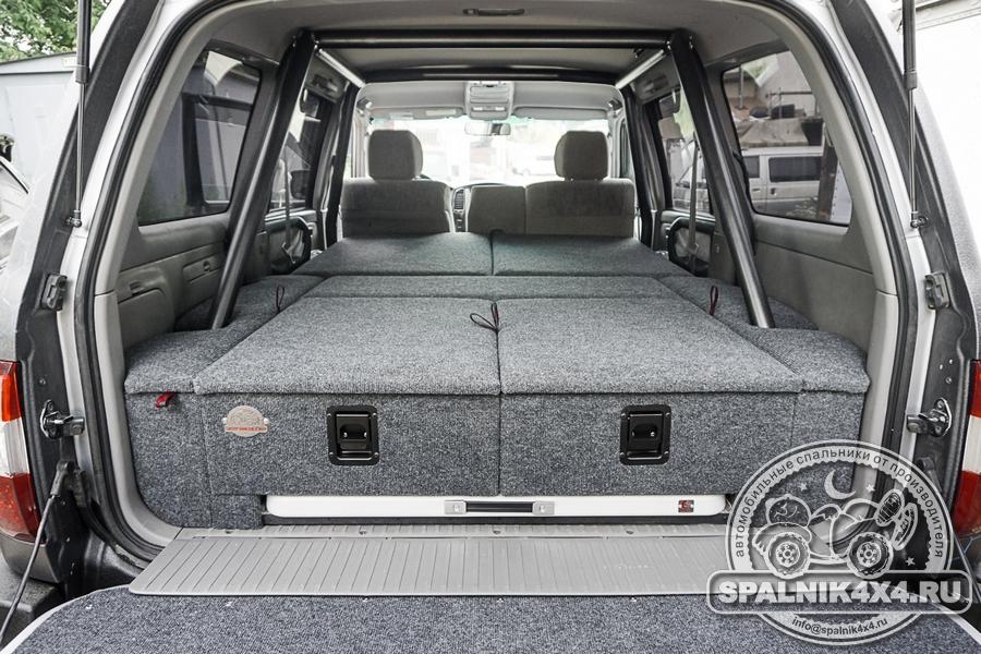 Автомобильный спальник с ящиками увеличенного объема, интегрированным столом и накладкой на заднюю дверь