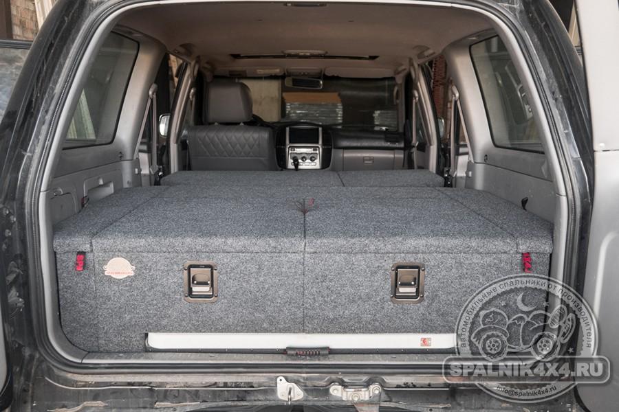 Toyota Land Cruiser 105 - автомобильный спальник с интегрированным столом и раскладываемыми элементами, прикрепленными к спинкам второго ряда сидений